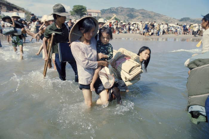 A woman in the foreground carrying a child wades through water