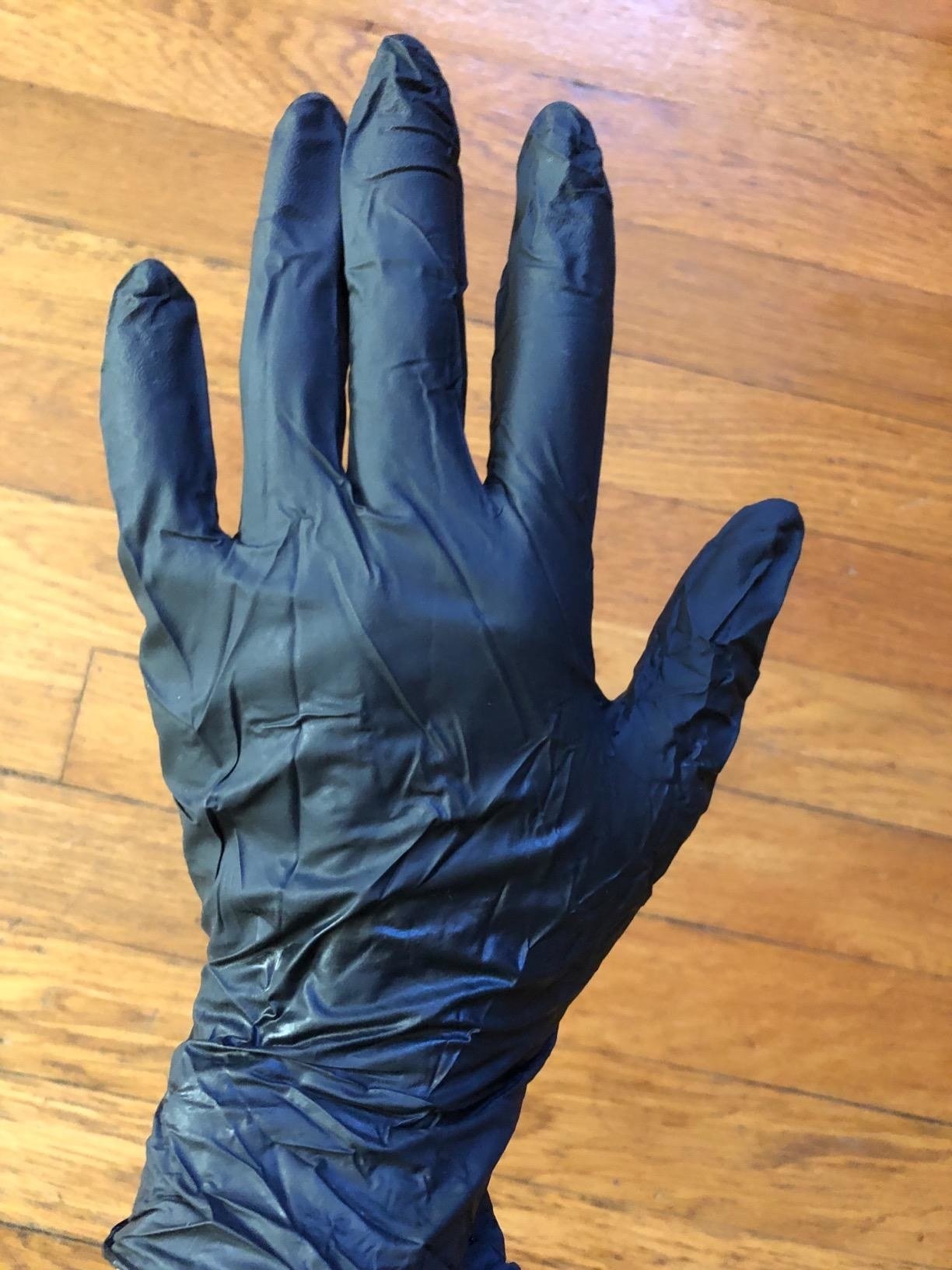 a reviewer's hand in the black glove