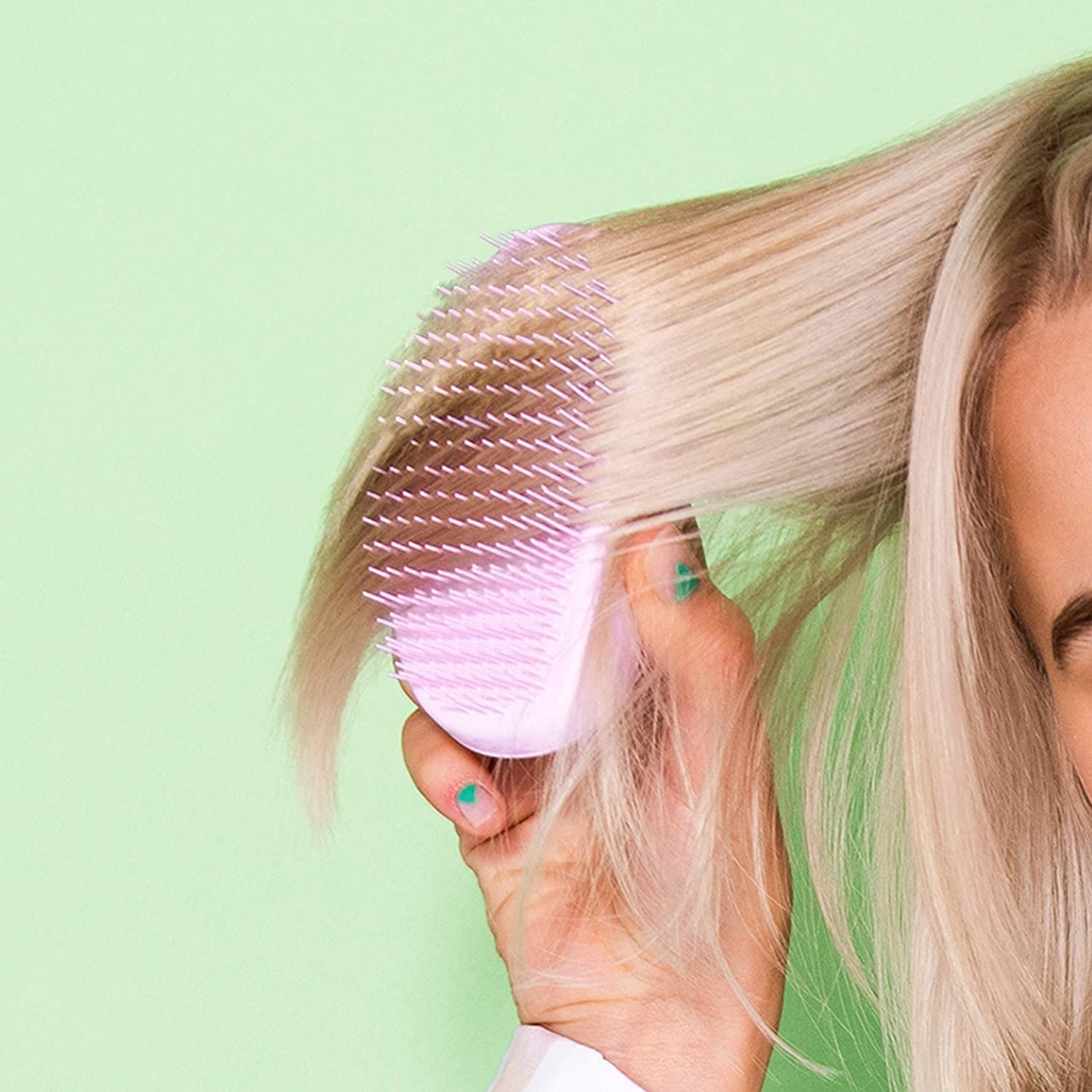A person brushing their hair with the Tangle Teezer