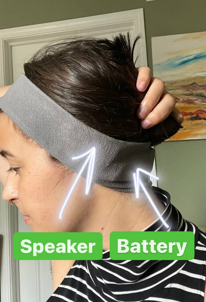 writer wearing the grey fleece circular headband with arrows pointing to the hidden speaker over her ear and the hidden battery pack at her neck
