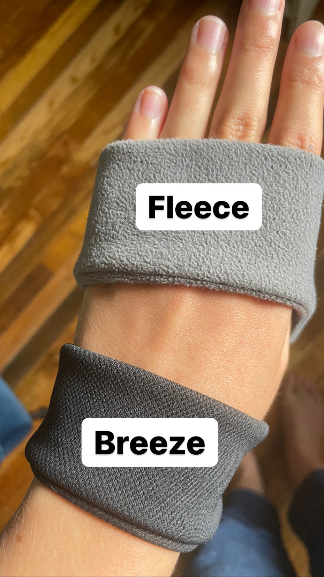 the writer with both headphones hanging from her wrist showing the fleece and breeze textures