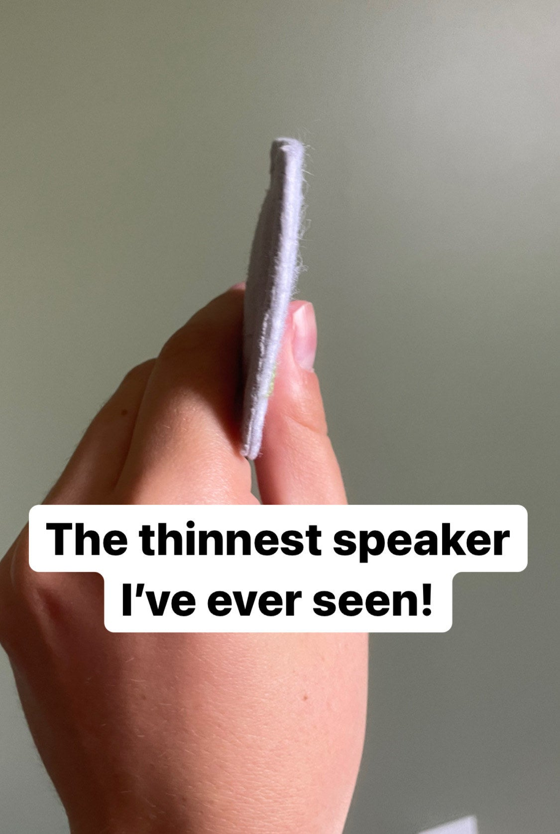 """the writer showing the super thin speaker from the side captioned """"the thinnest speaker I've ever seen"""""""