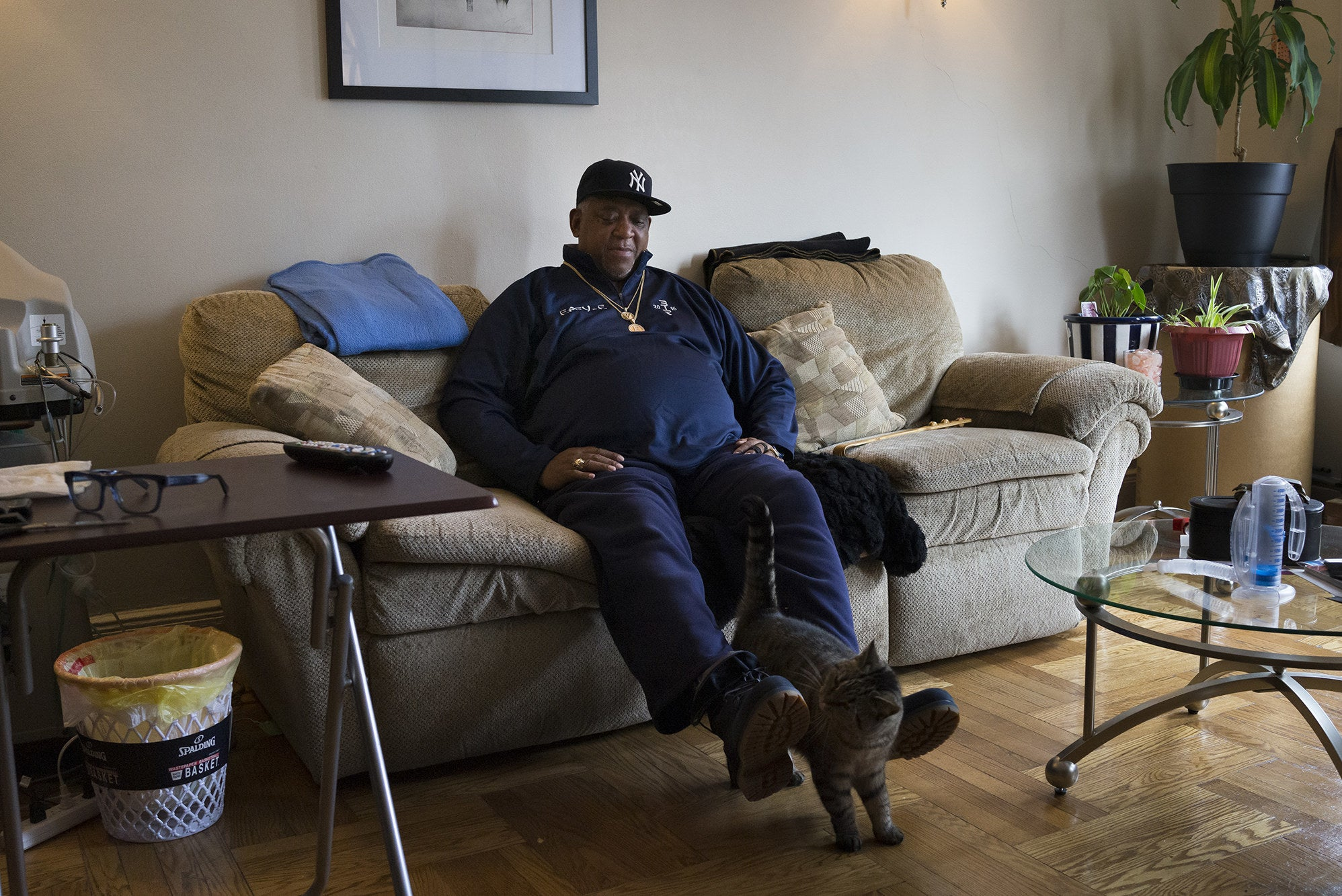 A man sits at home on his couch with a cat