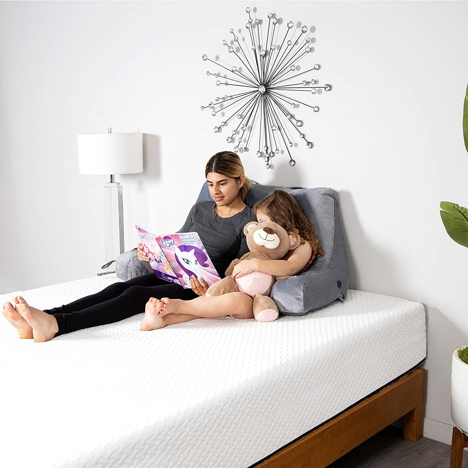 A person and a child reading with their backs against the pillow