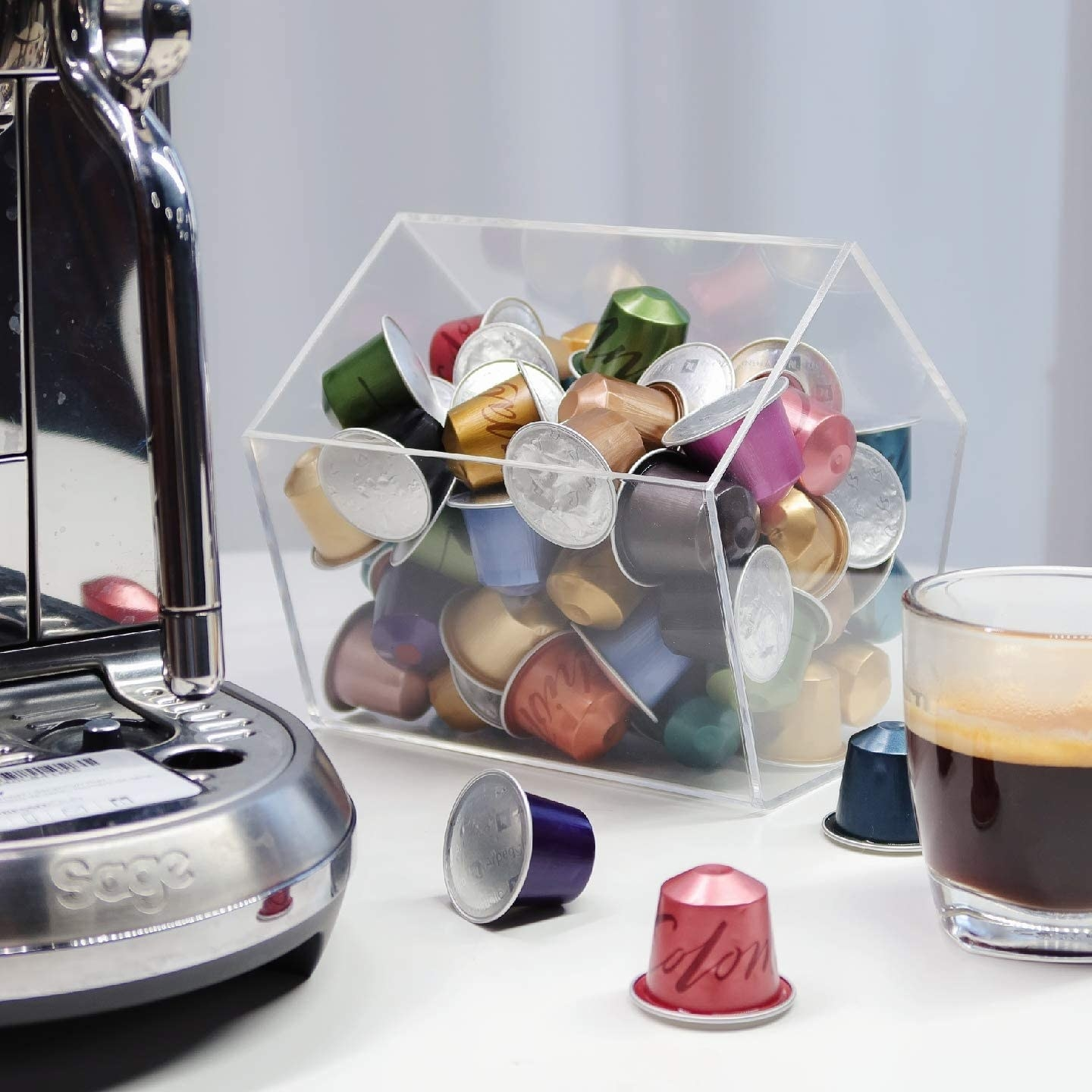 The plexiglass house filled with pods between a coffee machine and a cup of coffee