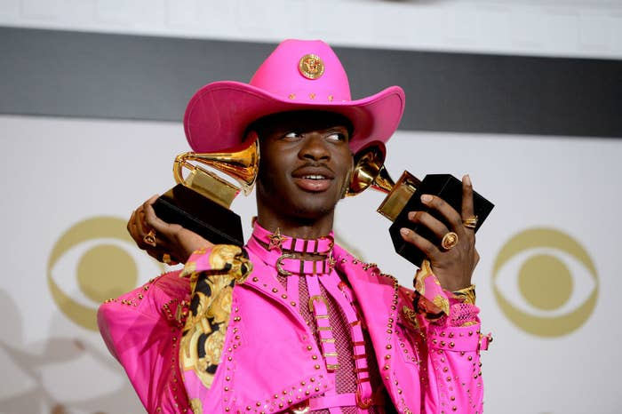 Lil Nas X holding his two Grammy Awards up to his ears backstage