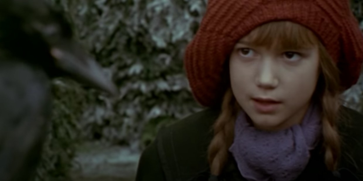 Mary looks at a crow while standing in a frost-covered garden