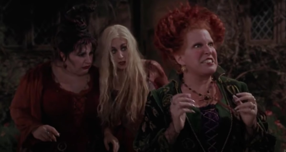 The Sanderson sisters stand in front of their house looking angry and perlexed