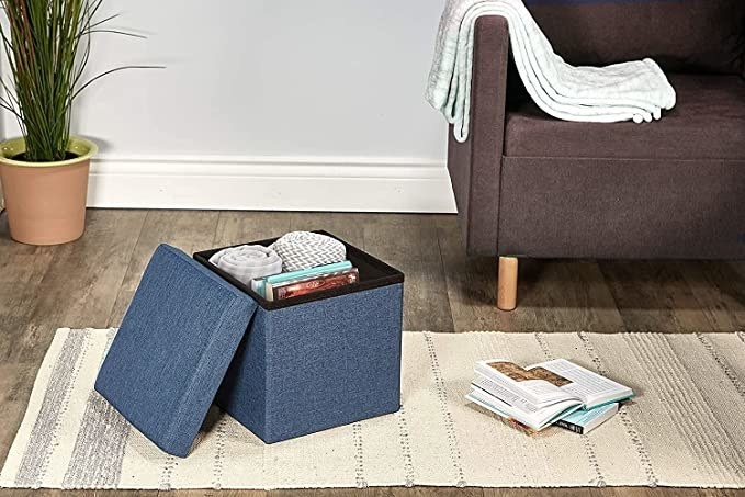 A blue ottoman with blankets and books stored in it