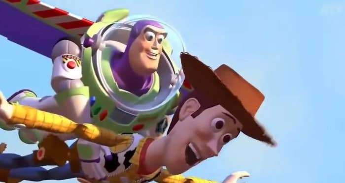 """Buzz holds onto Woody as they """"fly"""" in the sky"""