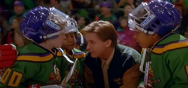 Coach Bombay talks to three of the Mighty Ducks in full gear