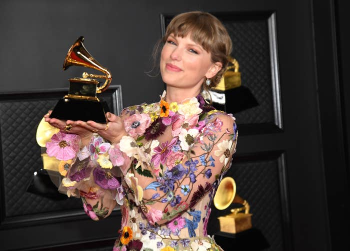 Taylor in a flowery outfit and holding up a Grammy