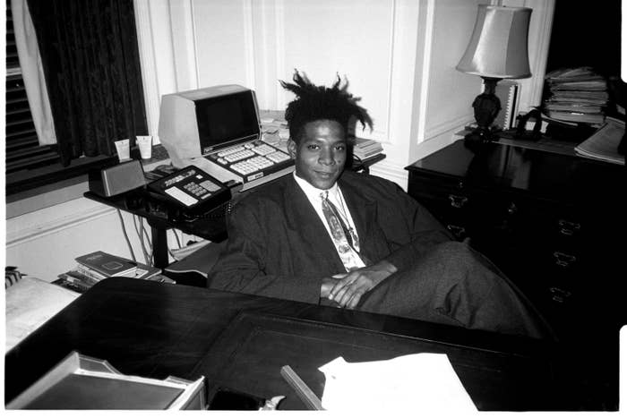 A black-and-white photo of Basquiat sitting at a desk in a suit and tie
