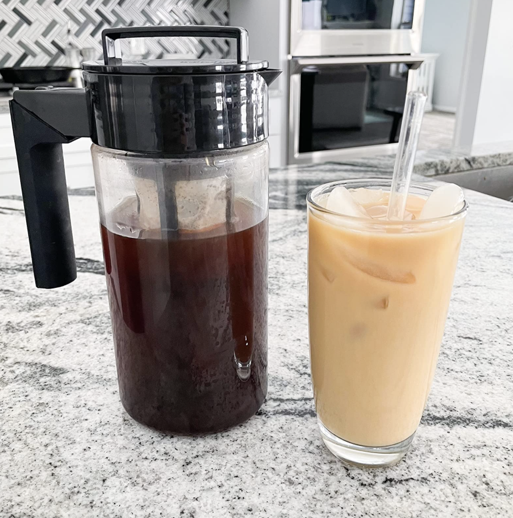 Pitcher of cold brew next to a cup of iced coffee