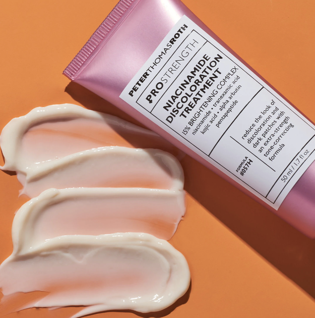 """A pink tube that says """"Peter Thomas Roth PRO Strength Niacinamide Discoloration Treatment"""" with a white-colored formula next to it"""