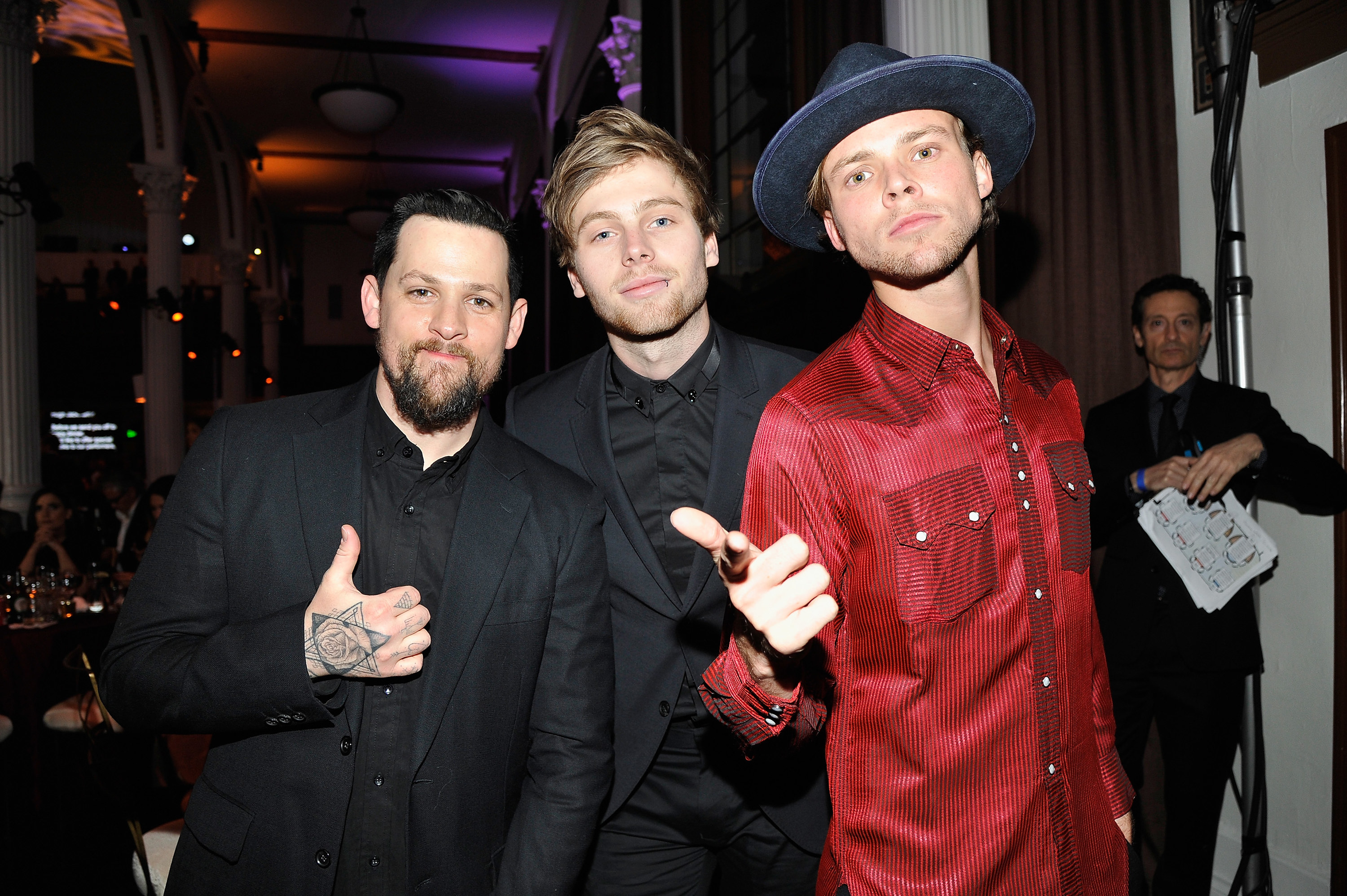 Luke and Michael Clifford posing with Joel Madden