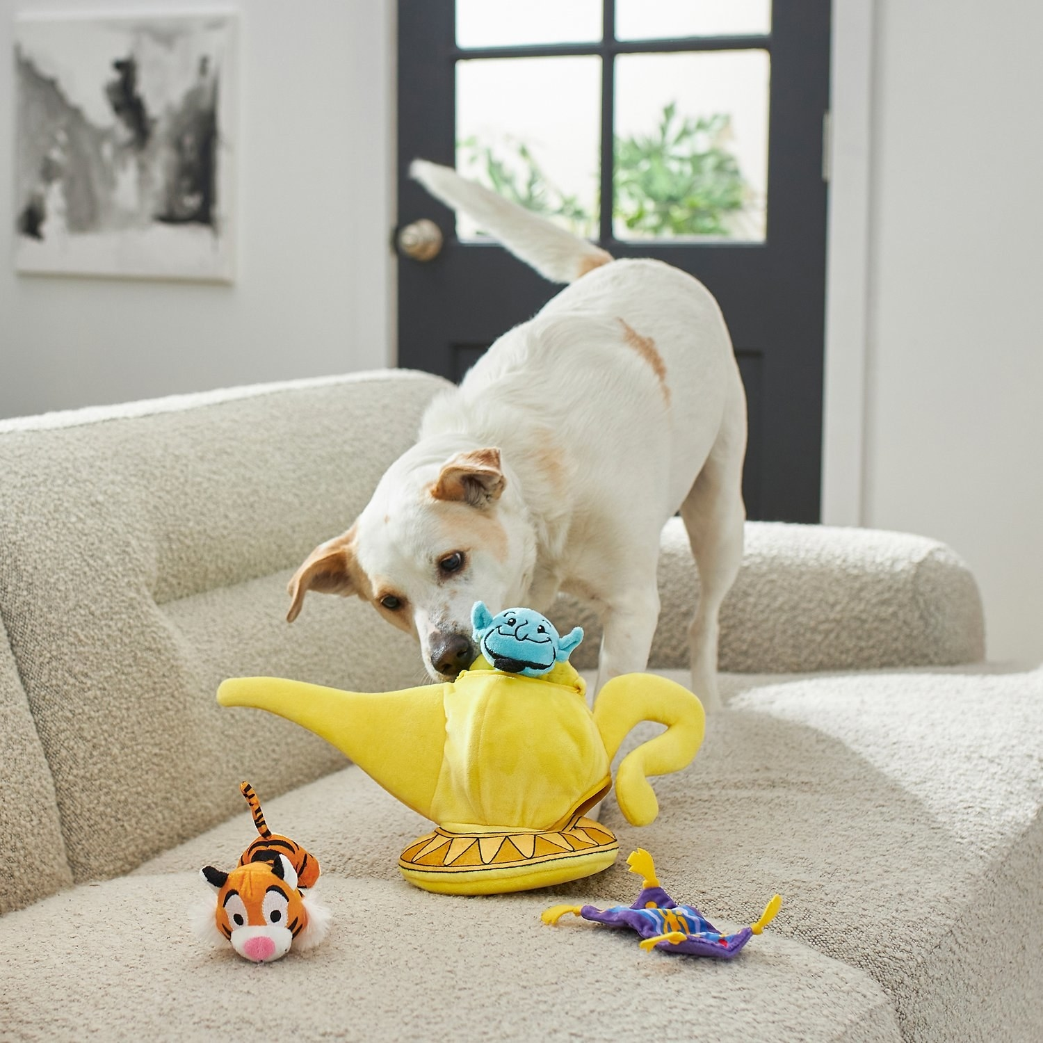a dog playing with a plush lamp and small genie, raja, and magic carpet toys