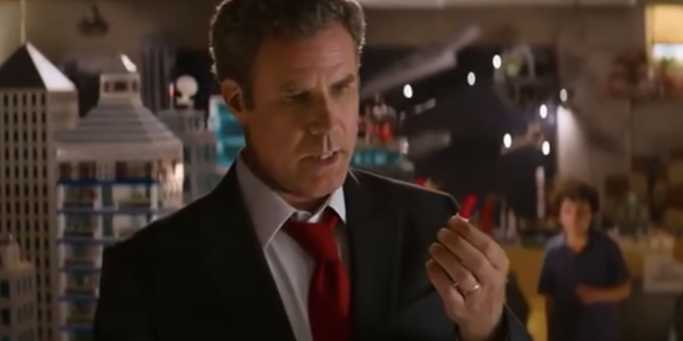 Will Ferrell as the dad, looking at a lego