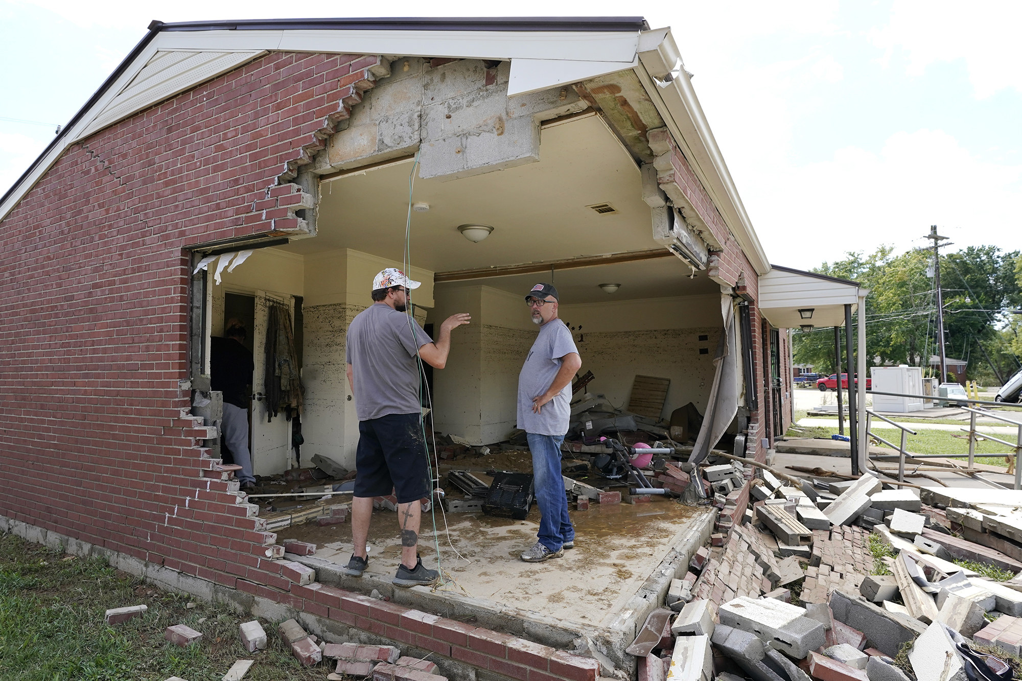 Two men stand inside a brick house with two perpendicular walls missing, bricks and concrete blocks scattered on the ground