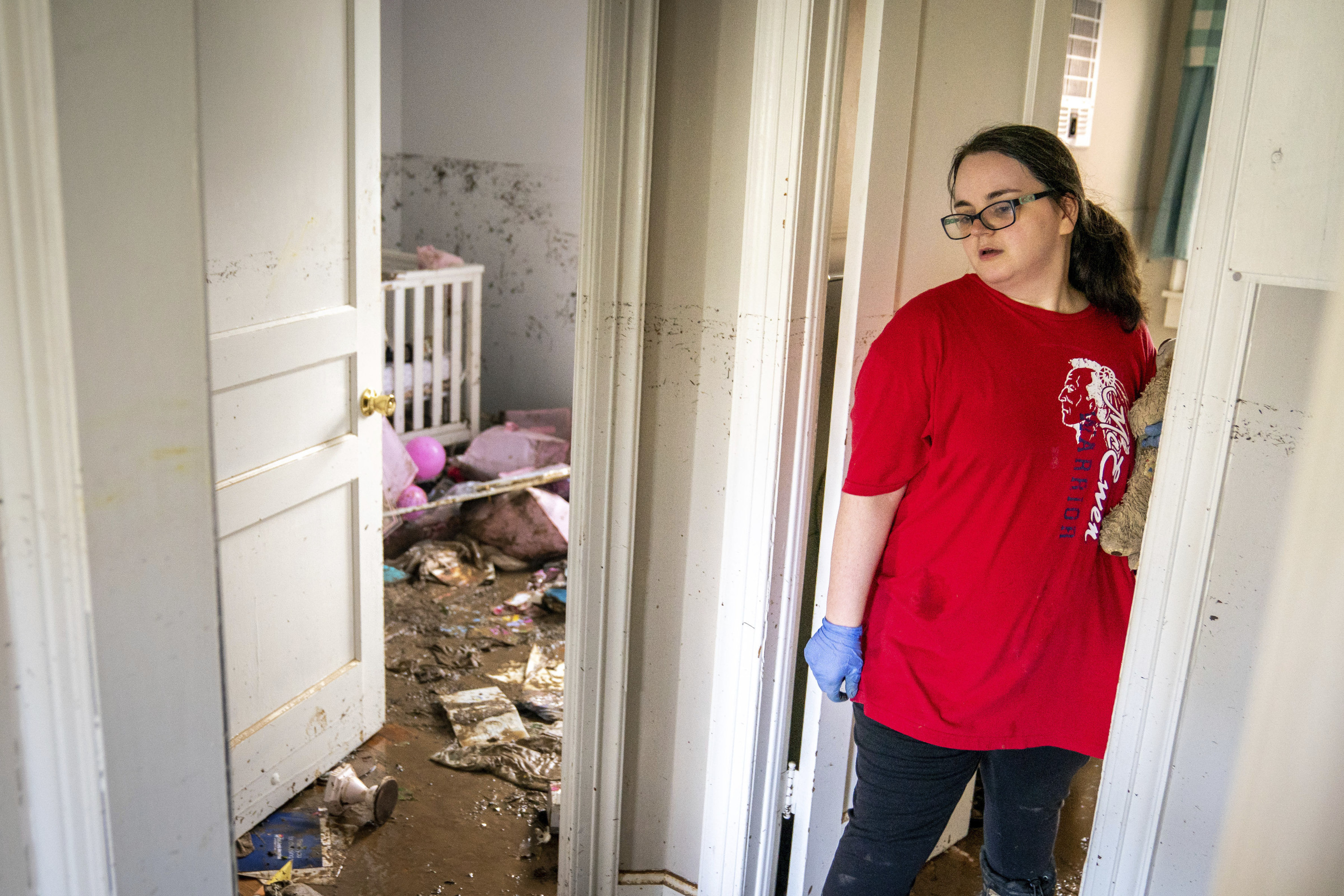 A woman stands by the doorway of a child's nursery with a muddy floor