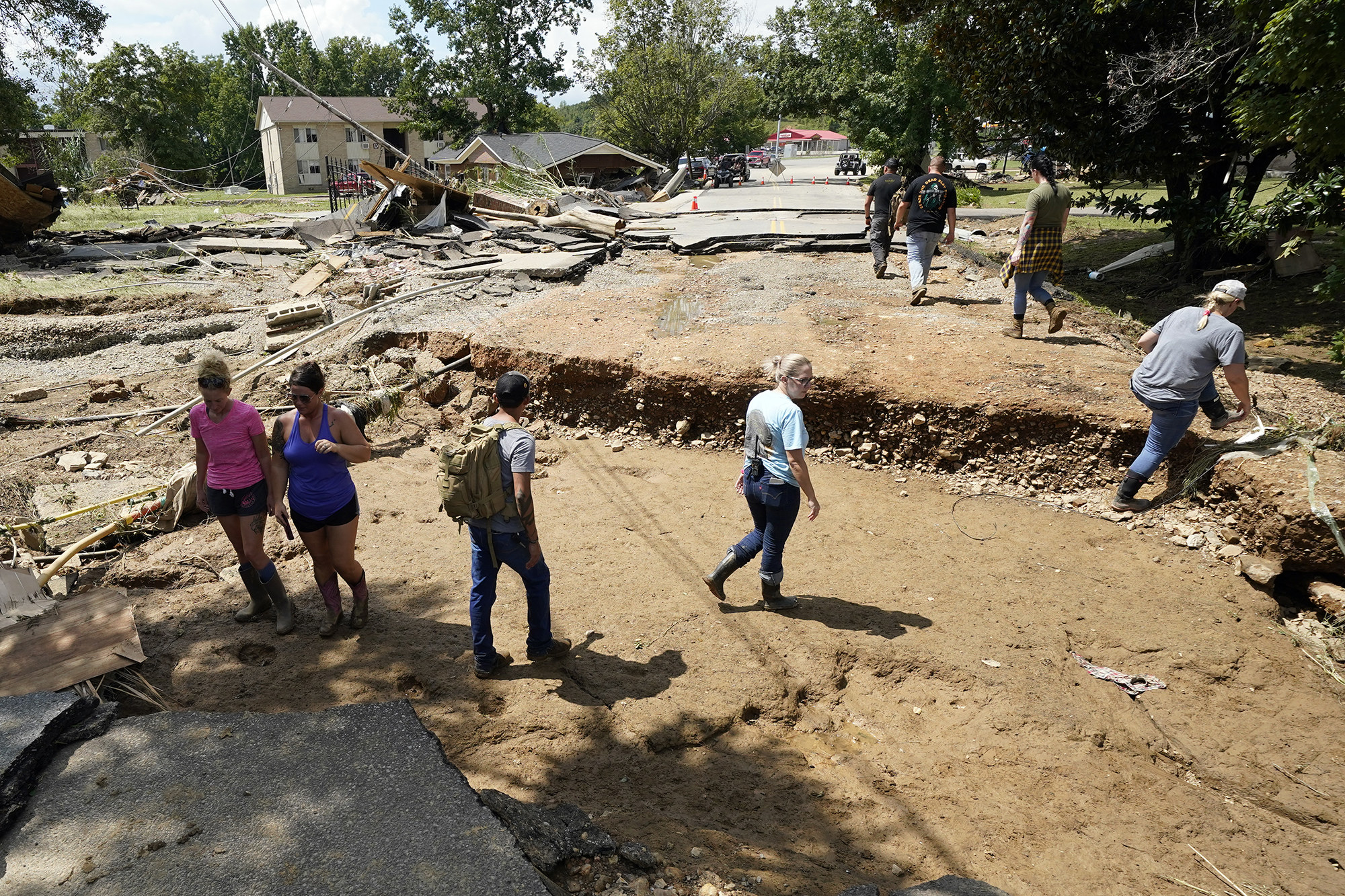 People walk through a dirt road where pavement and debris from collapsed homes litter the ground