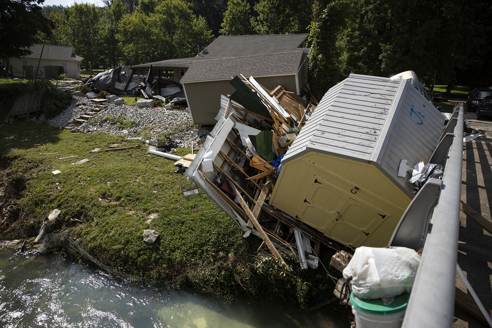 A shed with a destroyed wall leans beside a bridge into a creek