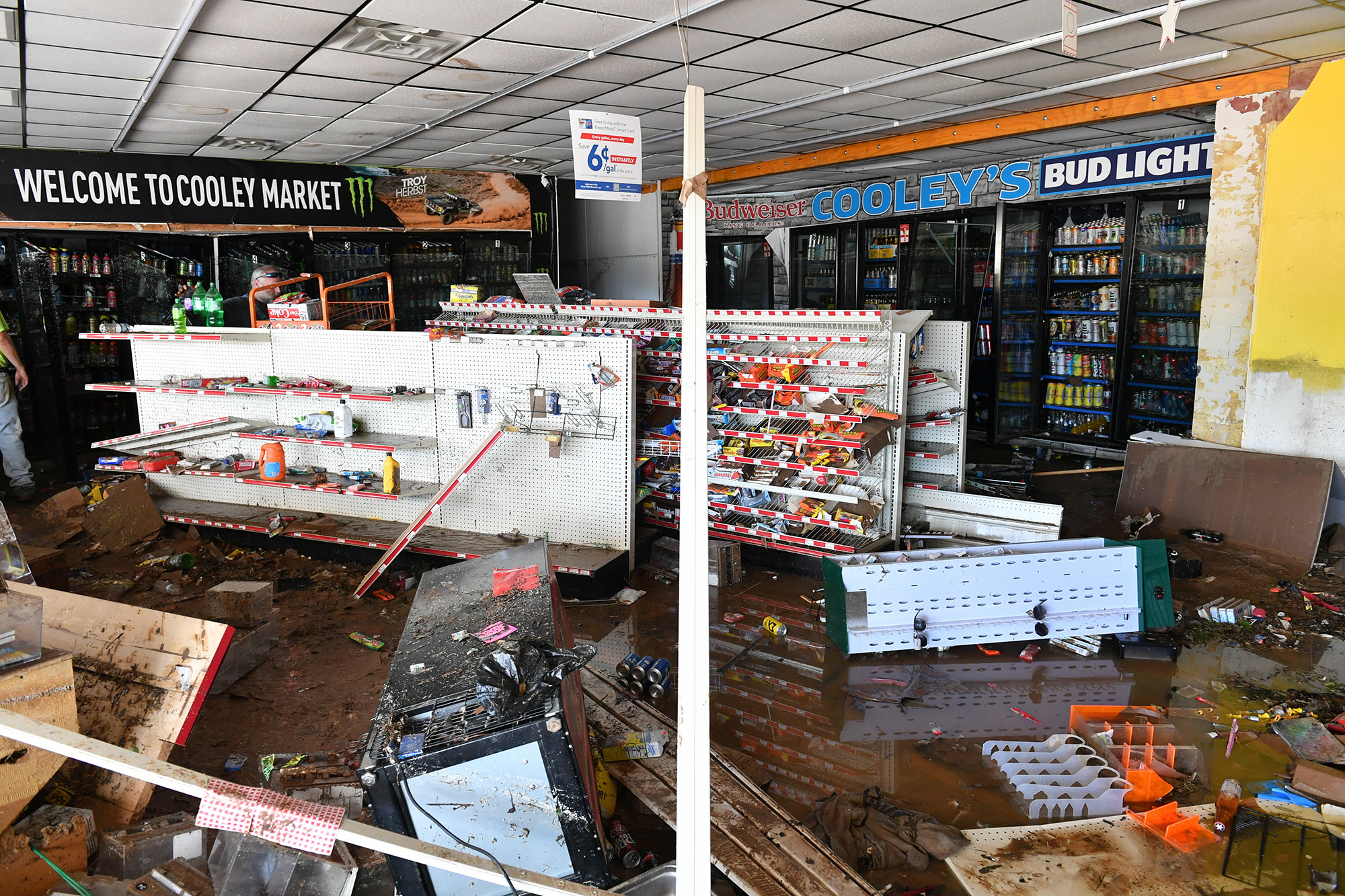 Aisles of candy and snacks are bare and toppled over in a flooded convenience store