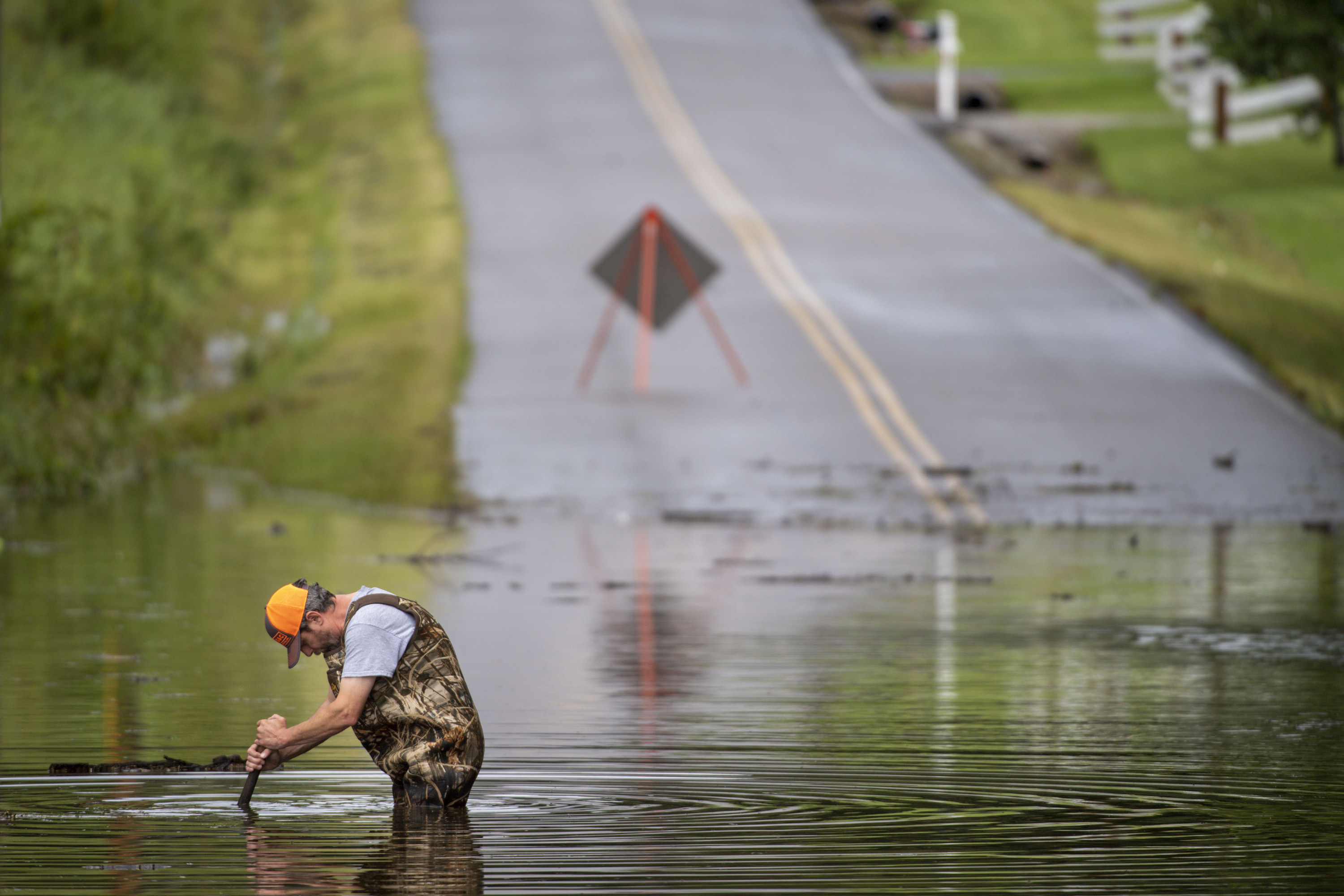 A man stands in waist-deep water on a flooded road, pushing a rod-like instrument below the surface