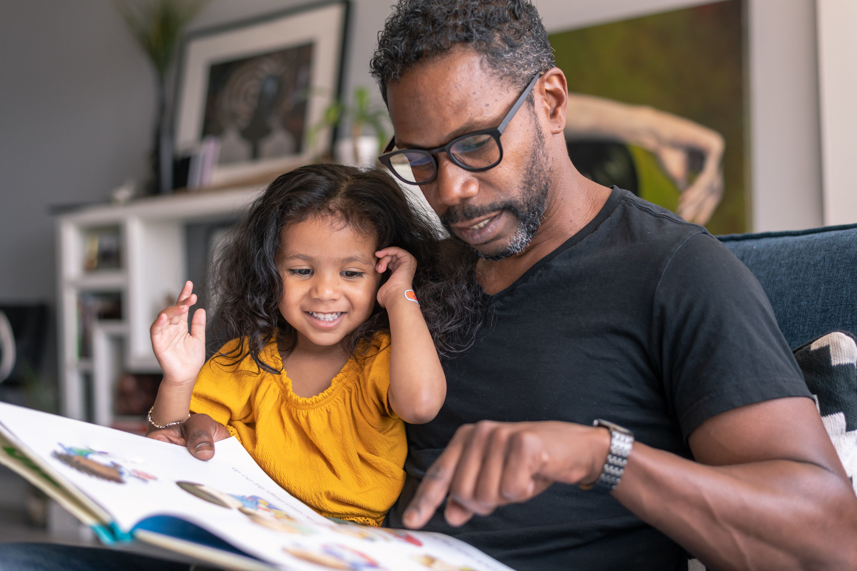 A dad reading to his daughter