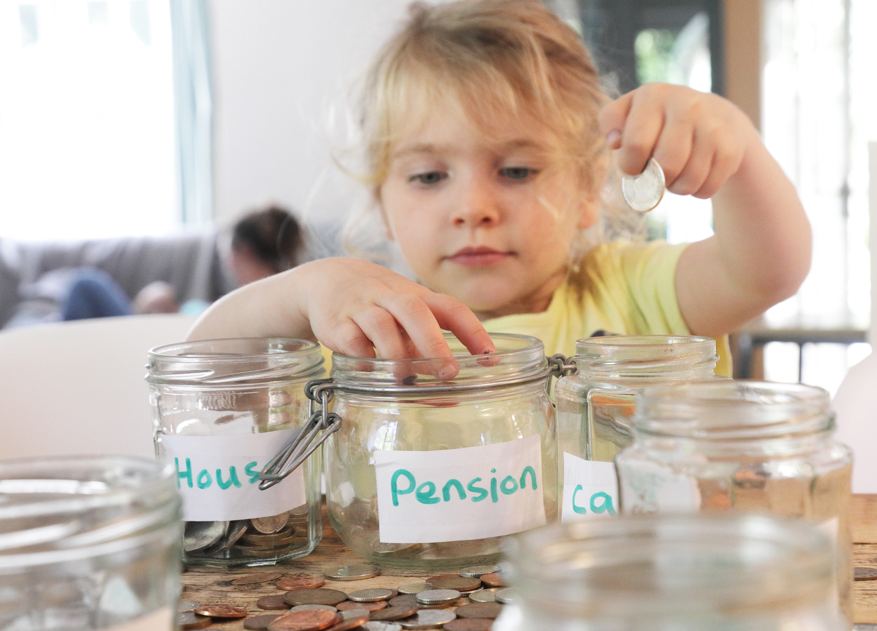 A young kid filling jars with money