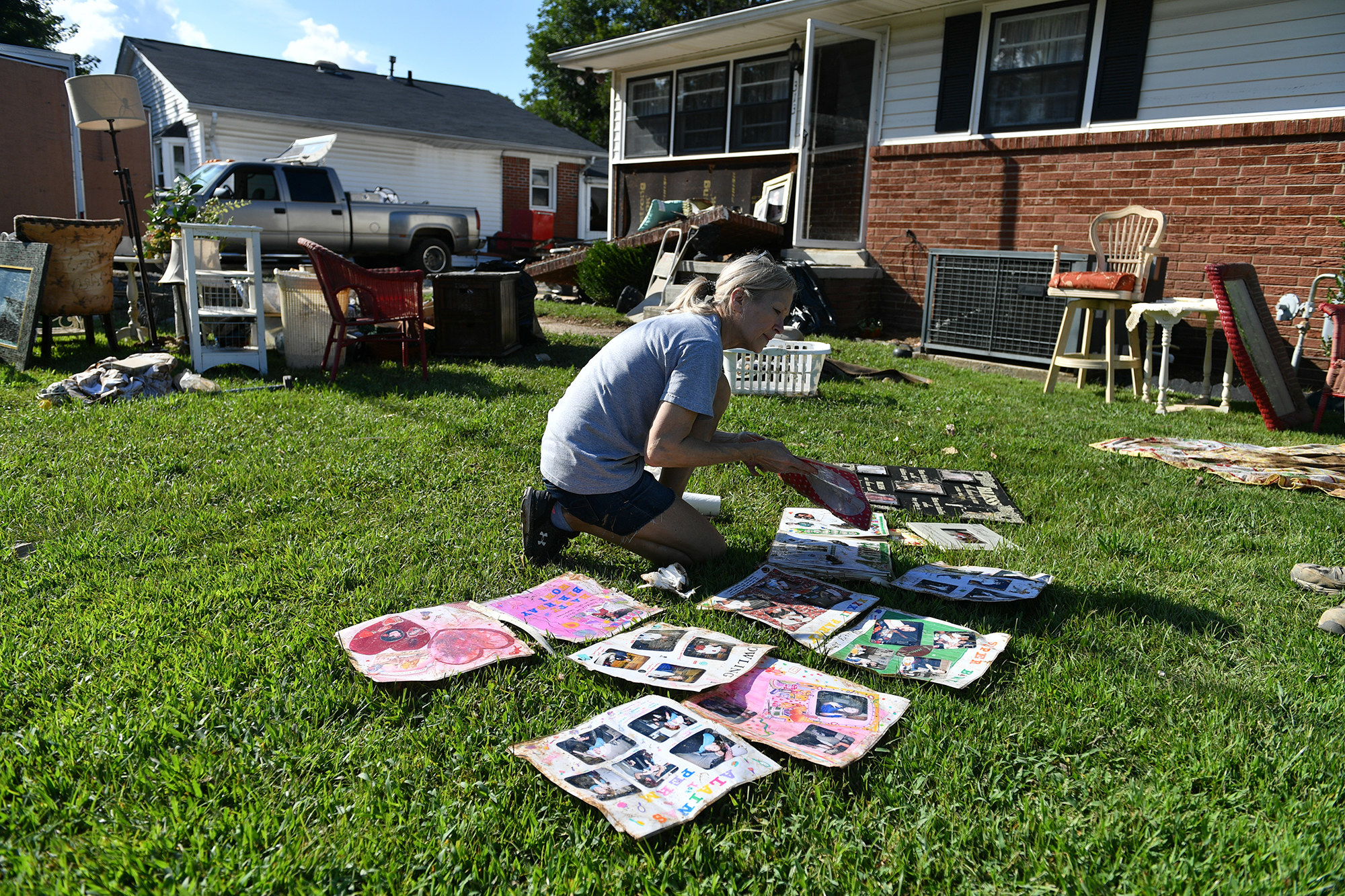 A woman places photos on their front lawn to dry