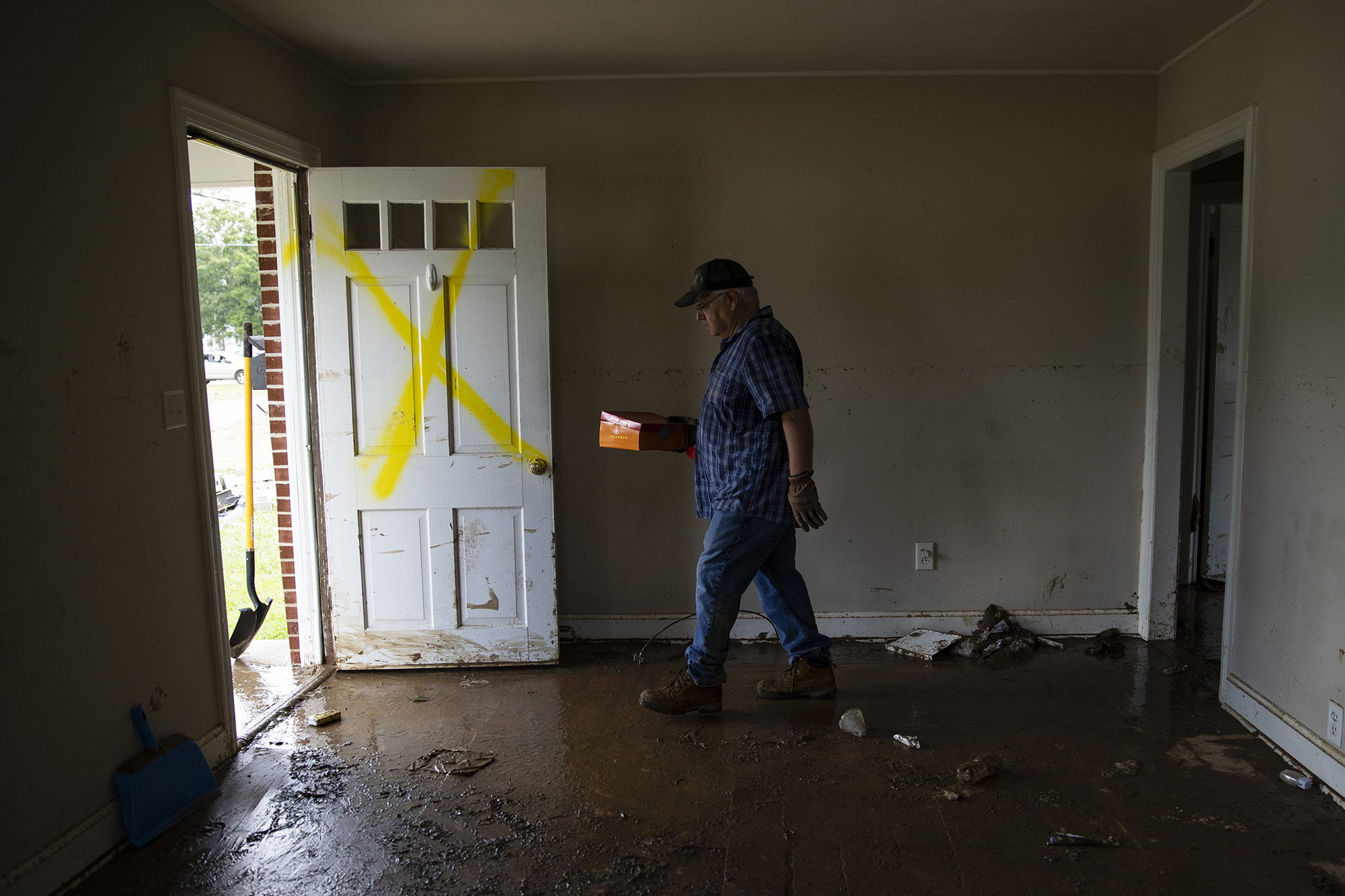 A man walks out of a house covered in mud with a spray-painted X on the door