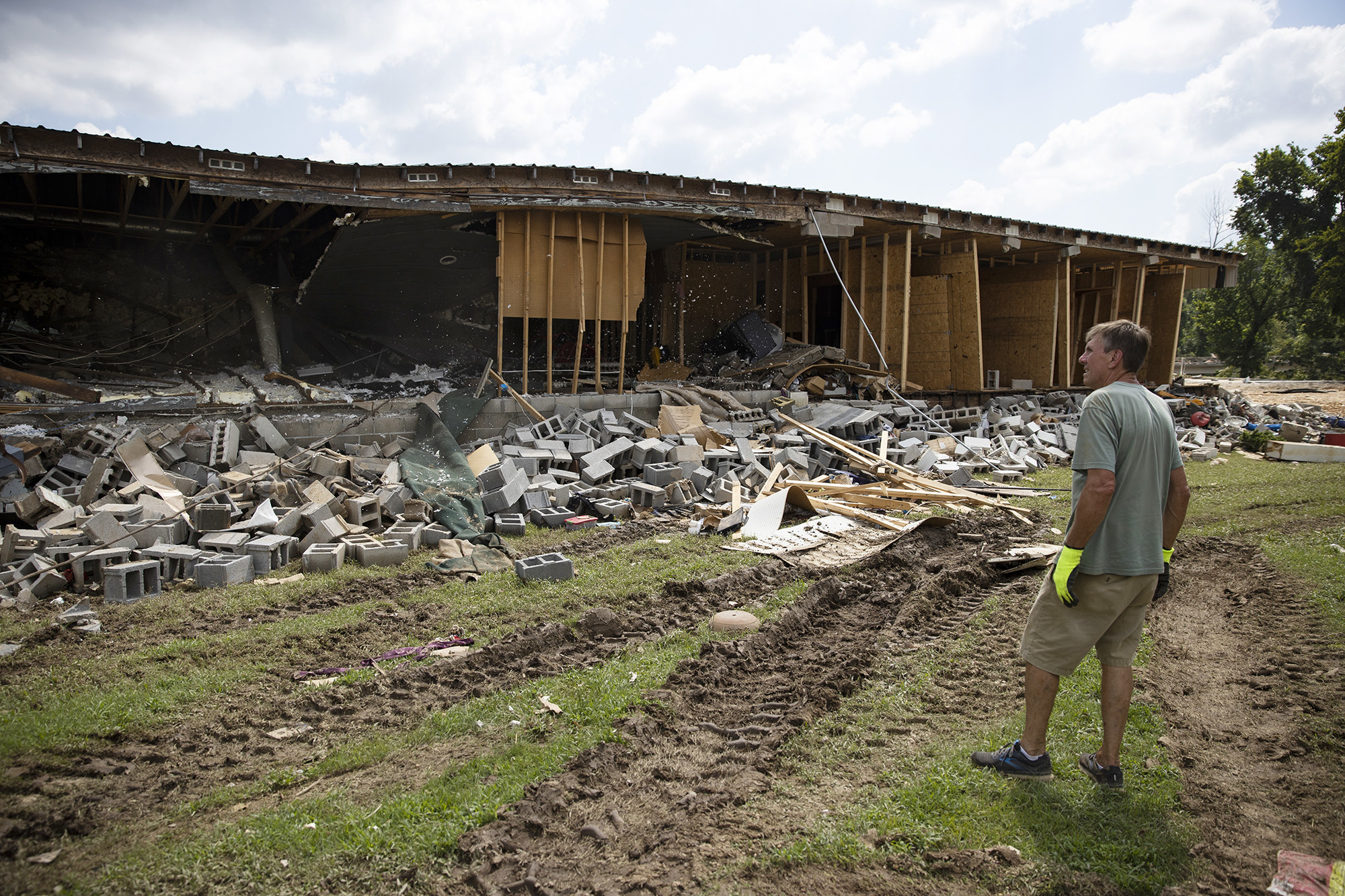 A man standing in a muddy field looks off-camera at the wreckage of a building