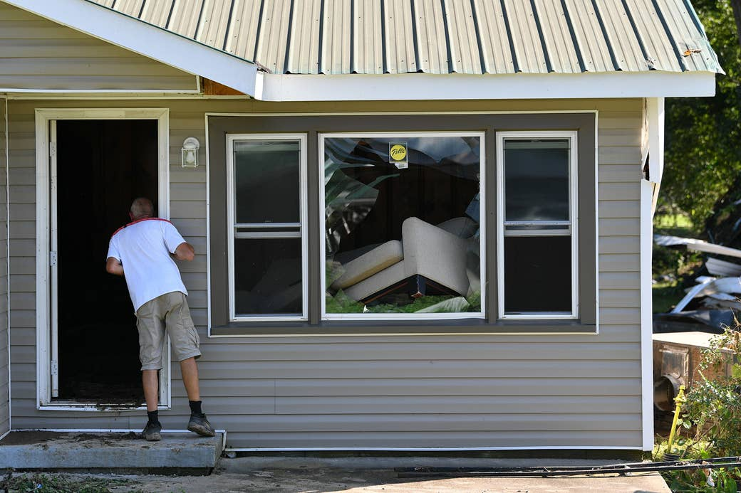 A man looks into a house where the picture window is broken with an askew sofa leaning through it