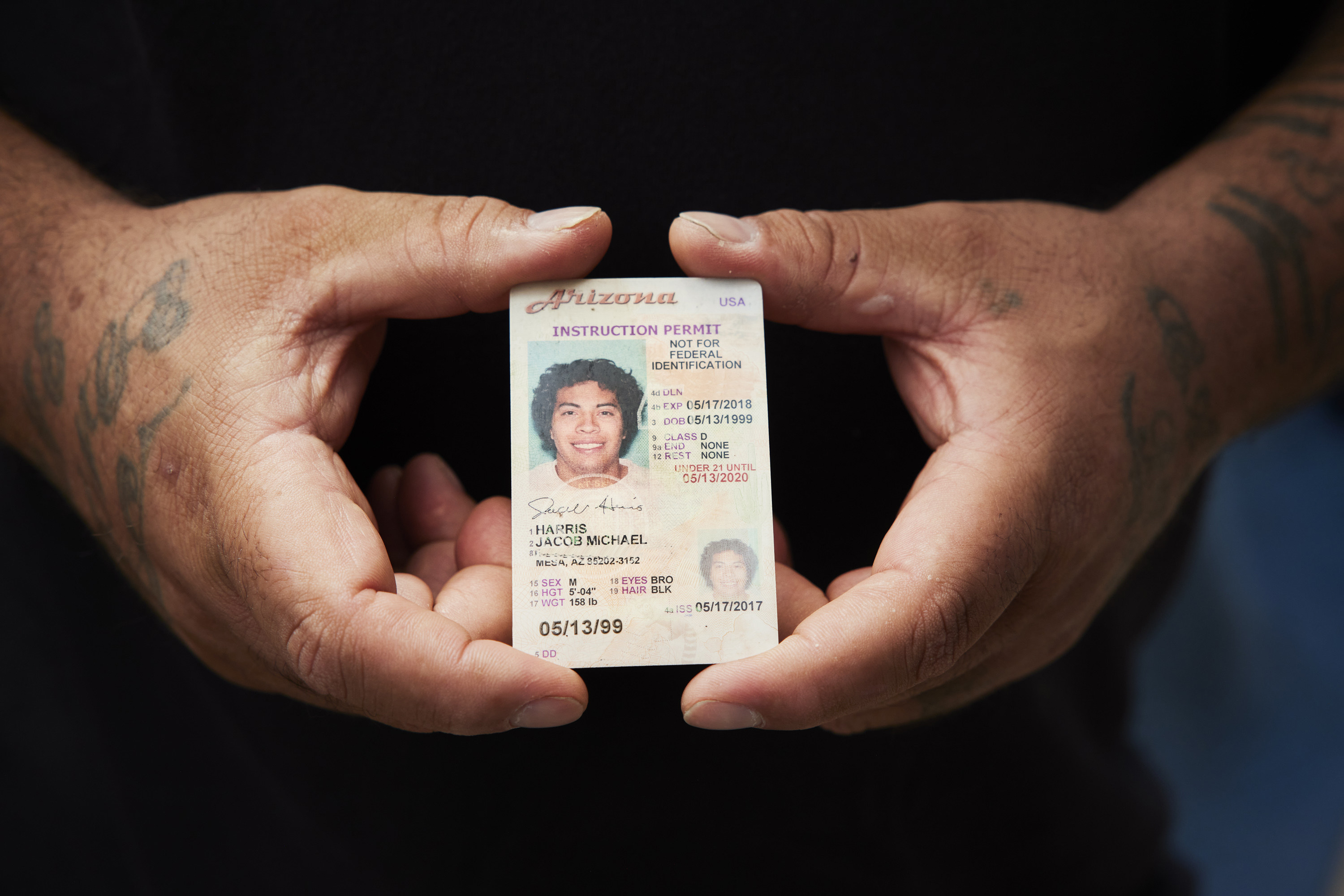 A man holds his son's learners permit between two hands