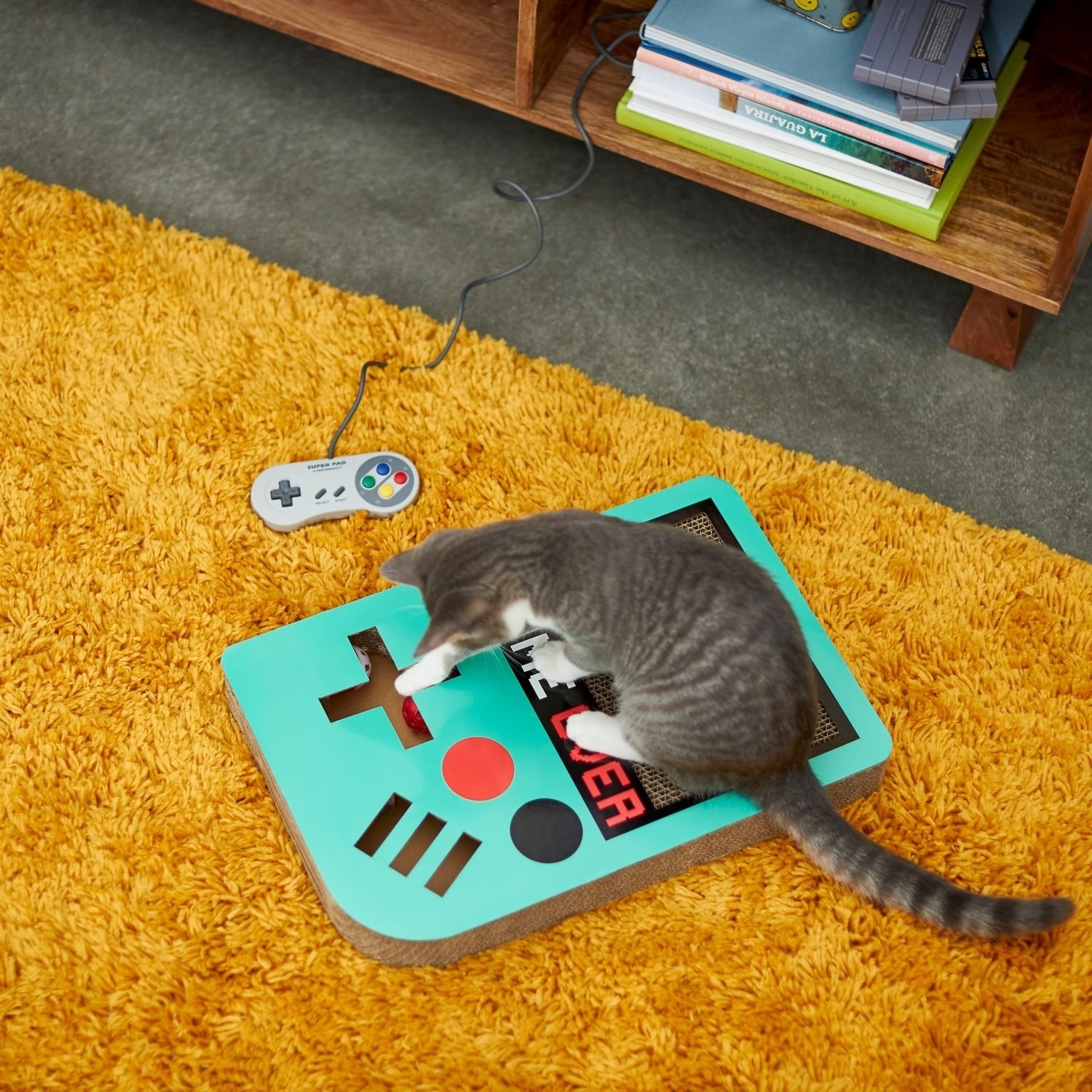 A cat on top of the video game scratcher