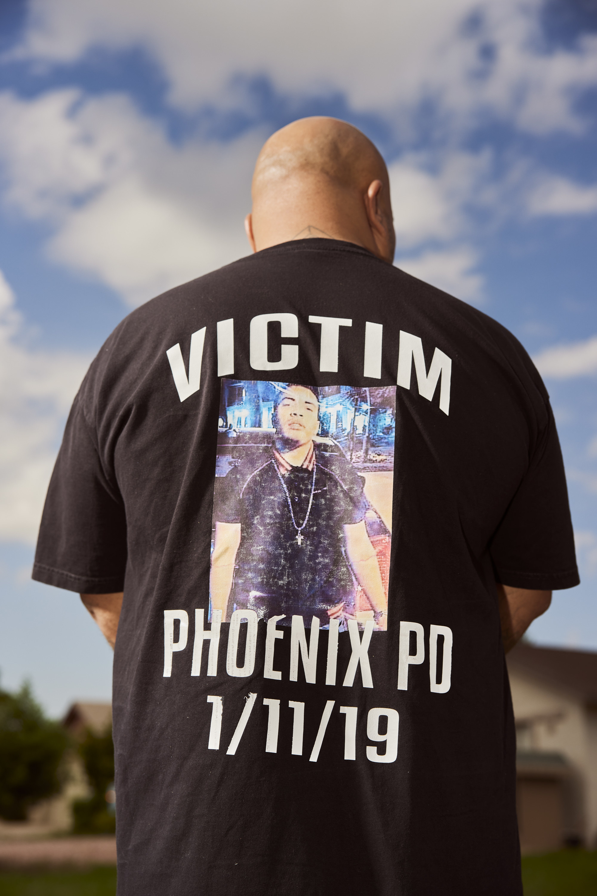 Roland photographed from the back, his T-shirt reads Victim Phoenix PD 1/11/19, with a photograph of Jacob