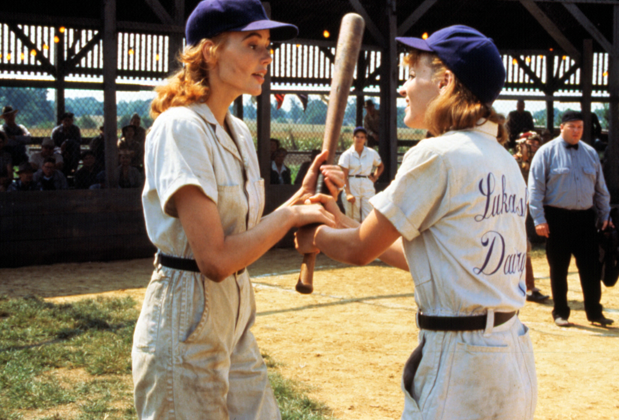 Geena Davis and Lori Petty fighting over a baseball bat.