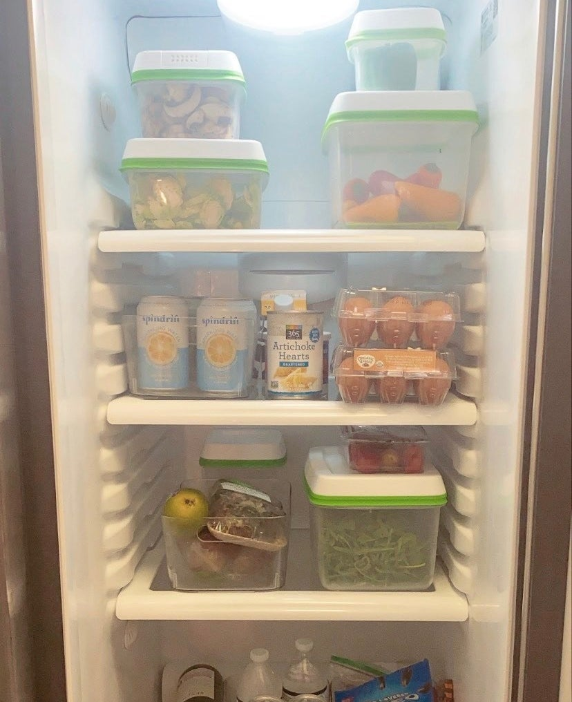 Inside of a fridge with various clear containers full of vegetables and fruit
