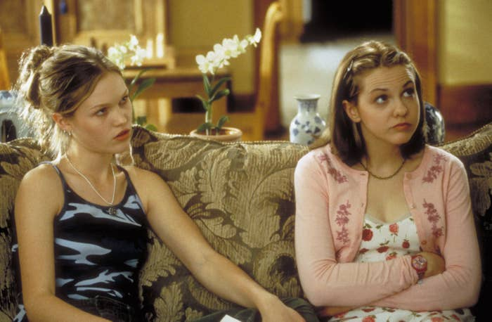 Julia Stiles and Laris Oleynik sitting on a couch and looking up.