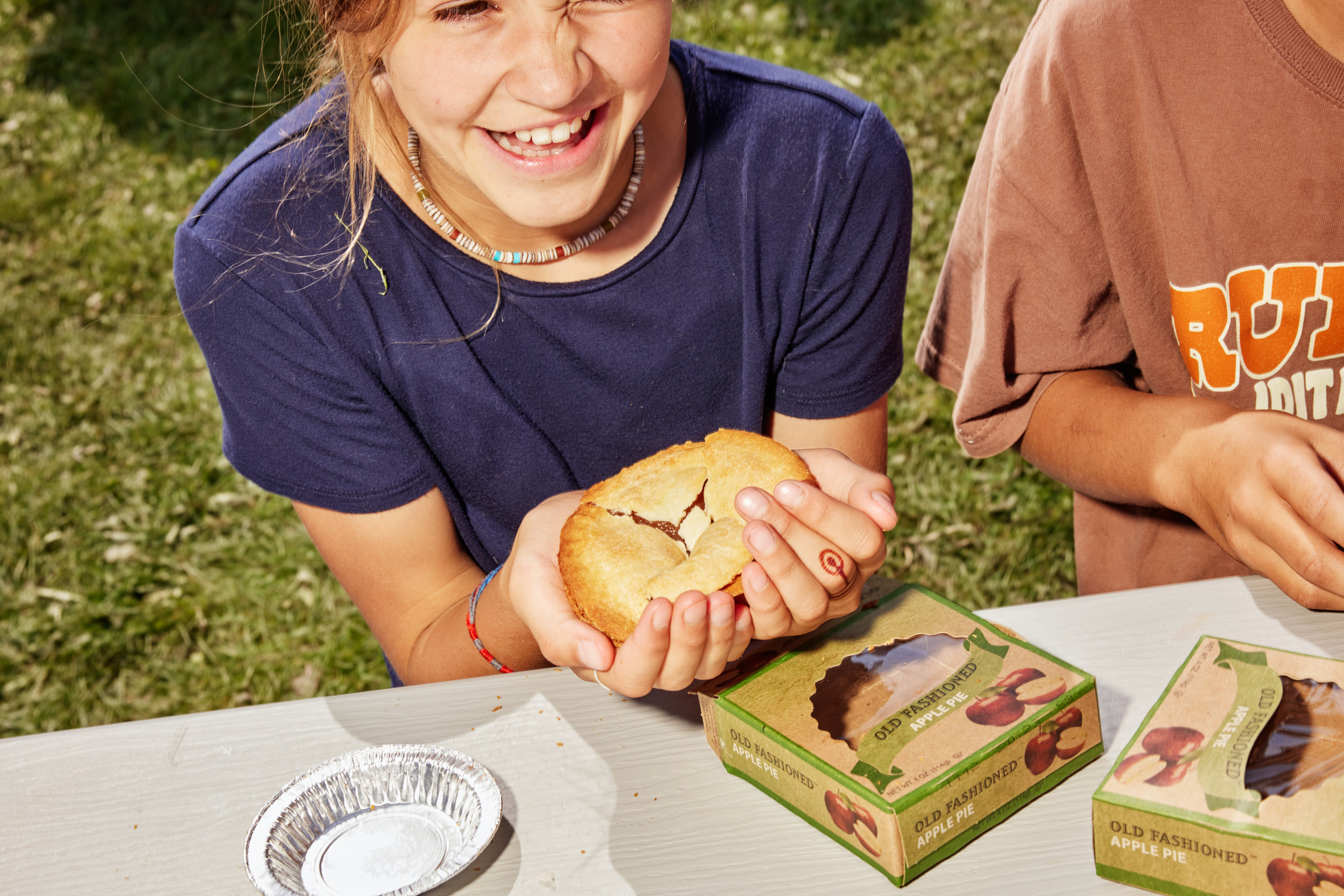 A young girl laughs while holding a small pie in her hands