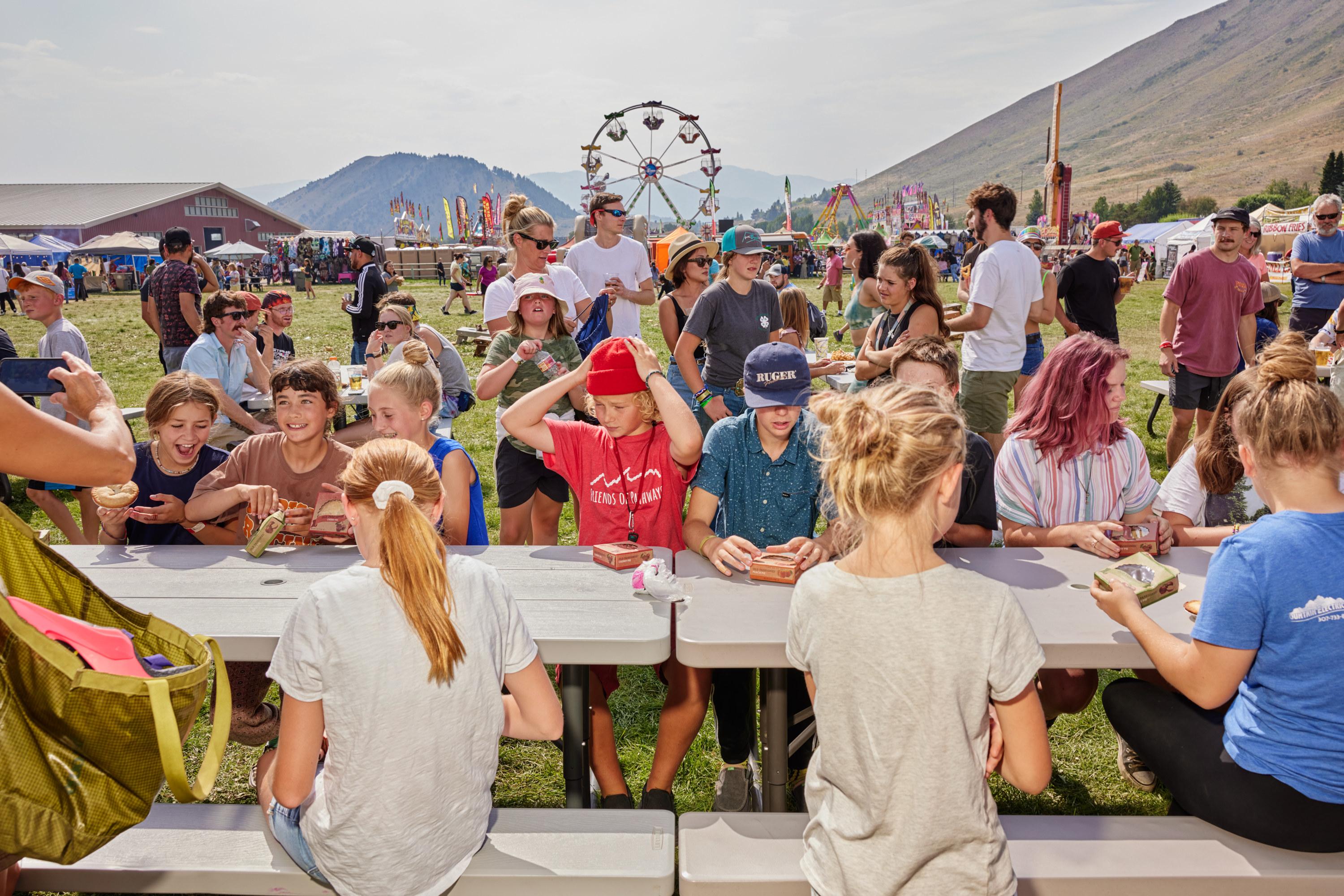 Children sitting at a picnic table with small pies, a ferris wheel, and parents in the background