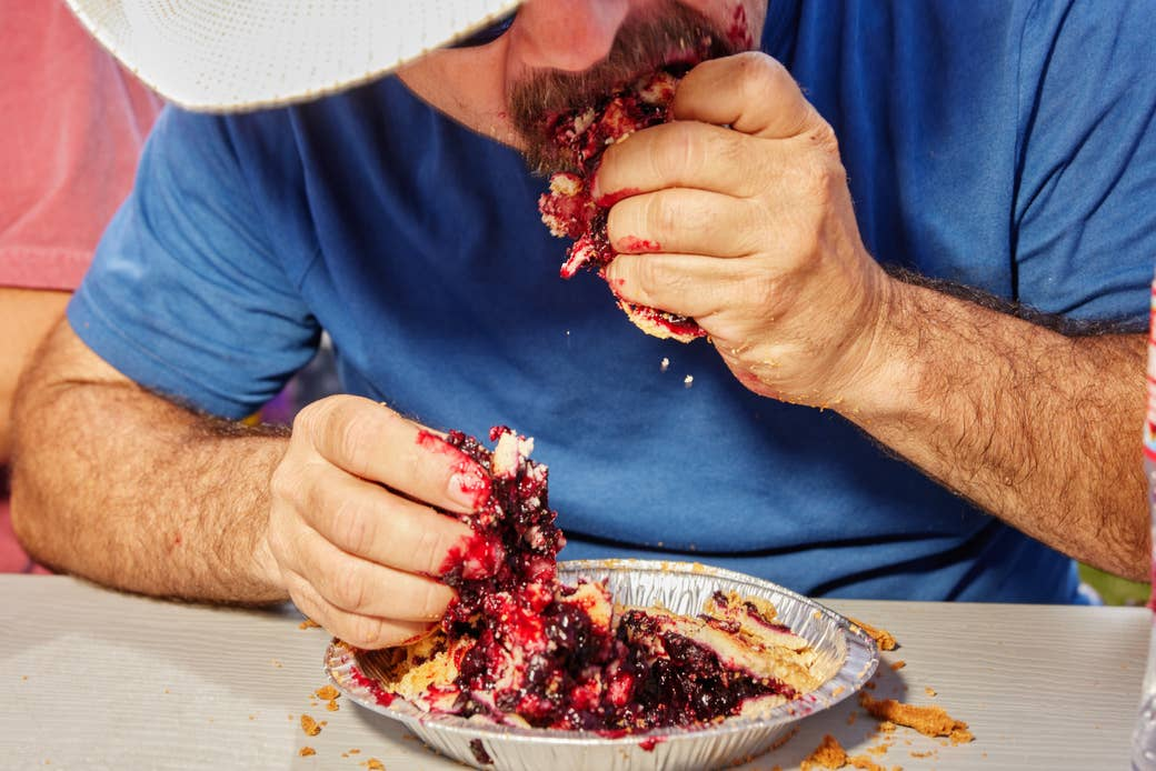 A man's hands as he shovels berry pie into his face