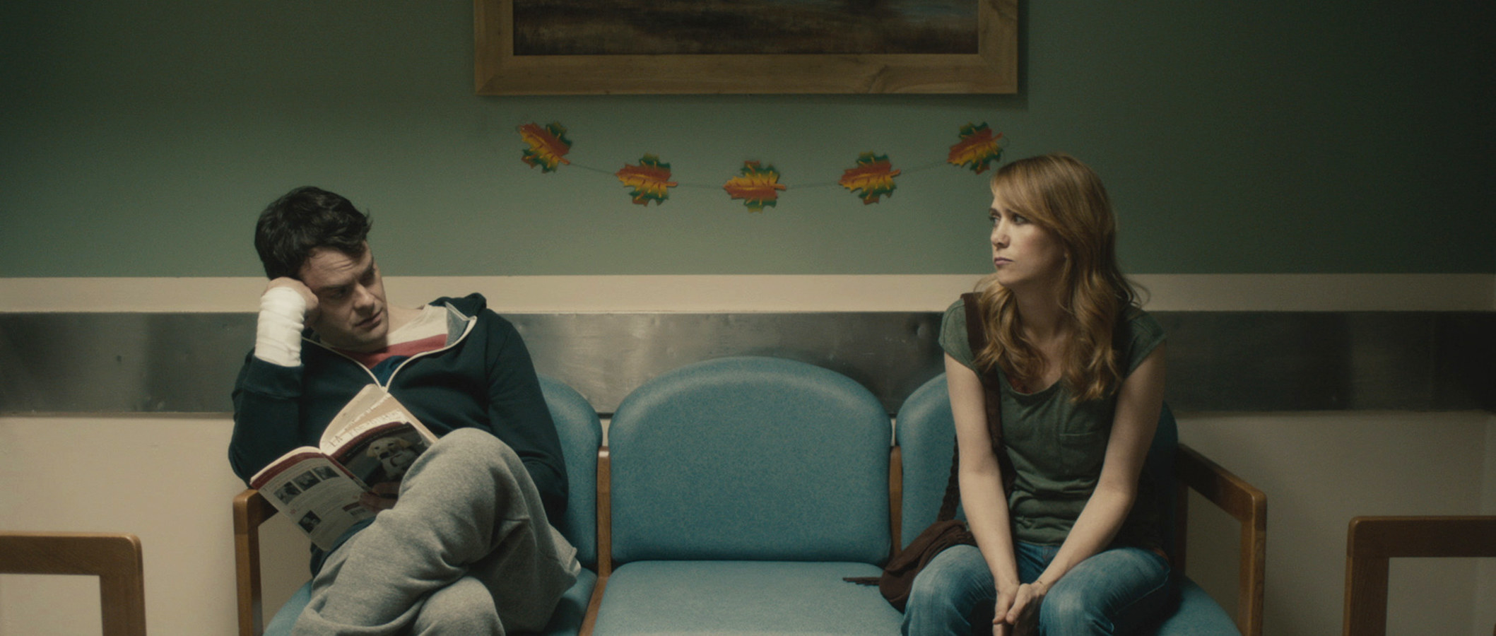 Bill Hader is holding a book and looking at Kristen Wiig.