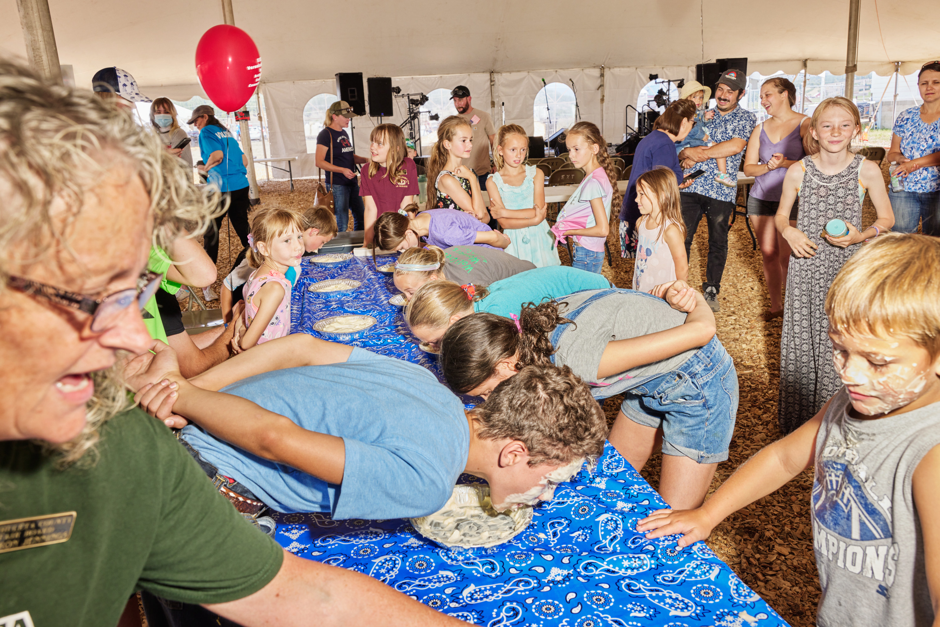 Two long rows of children with their heads bent down over a long table eating pie as a crowd looks on