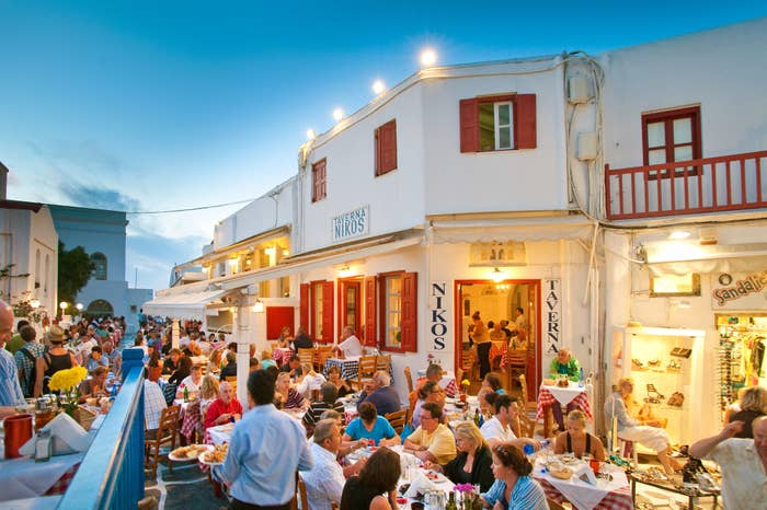 A busy restaurant outdoors in Greece.