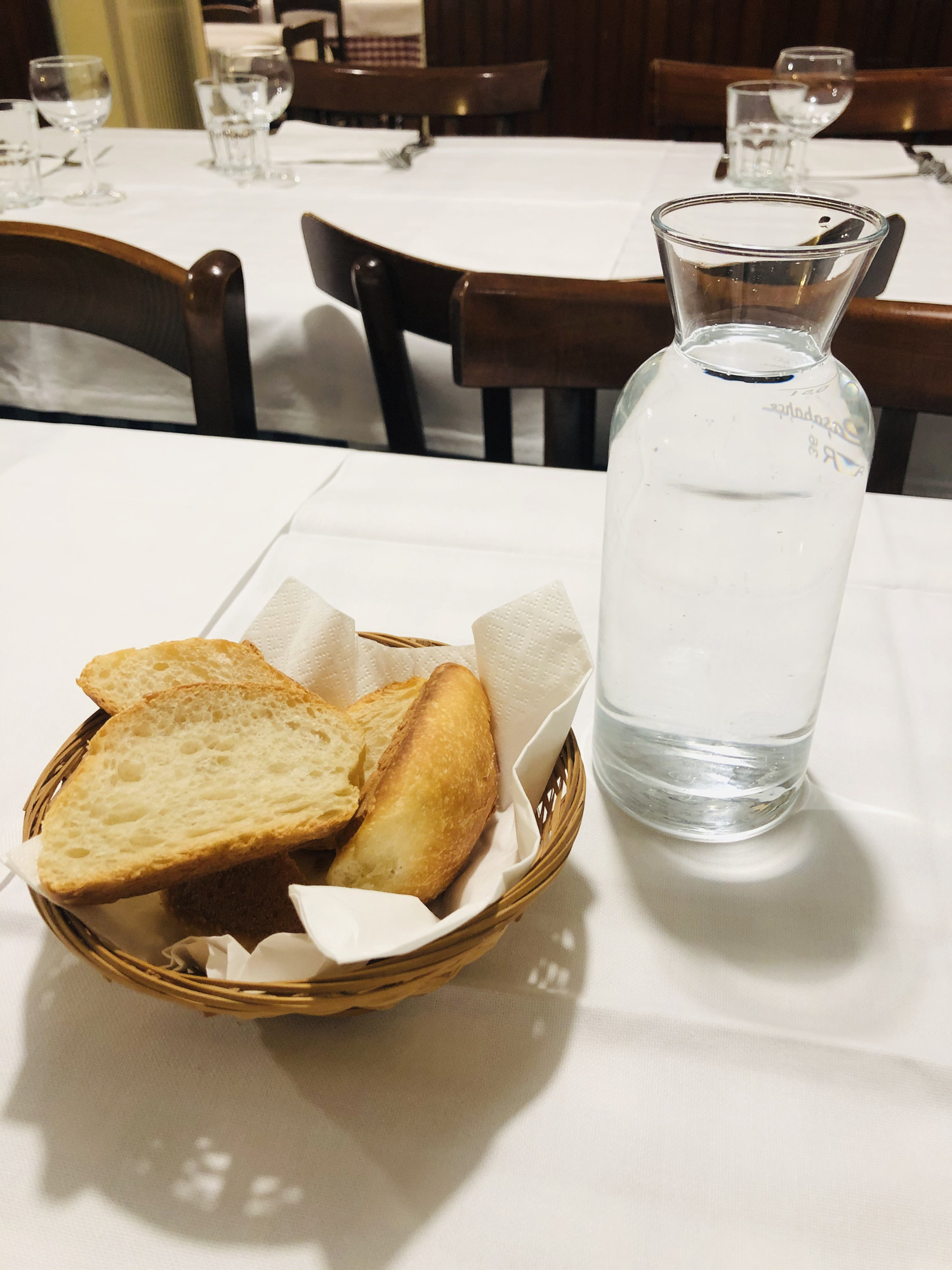 A bread basket on a table at a restaurant.