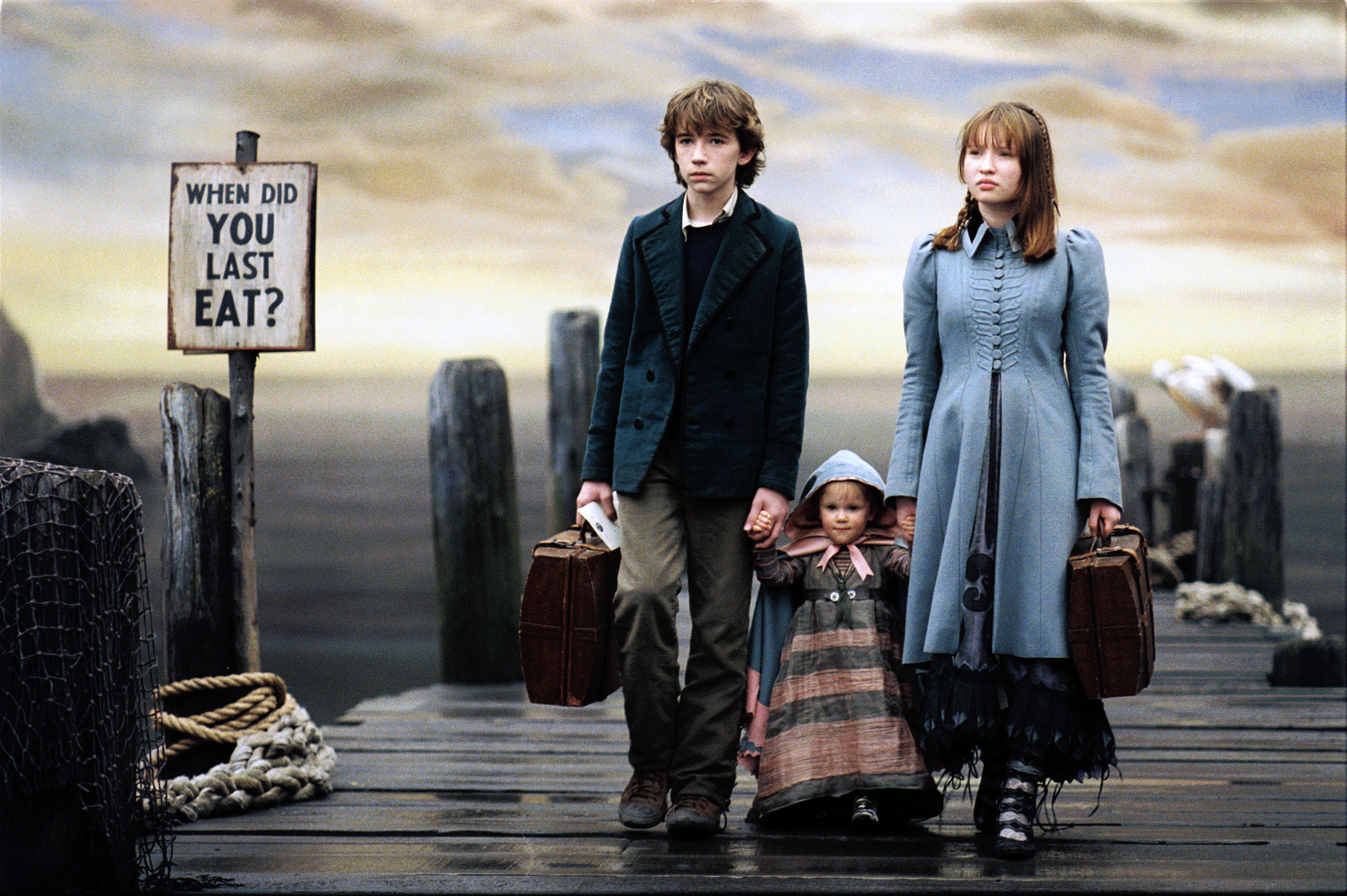 Liam Aiken, Kara/Shelby Hoffman, and Emily Browning holding hands while walking on a dock.