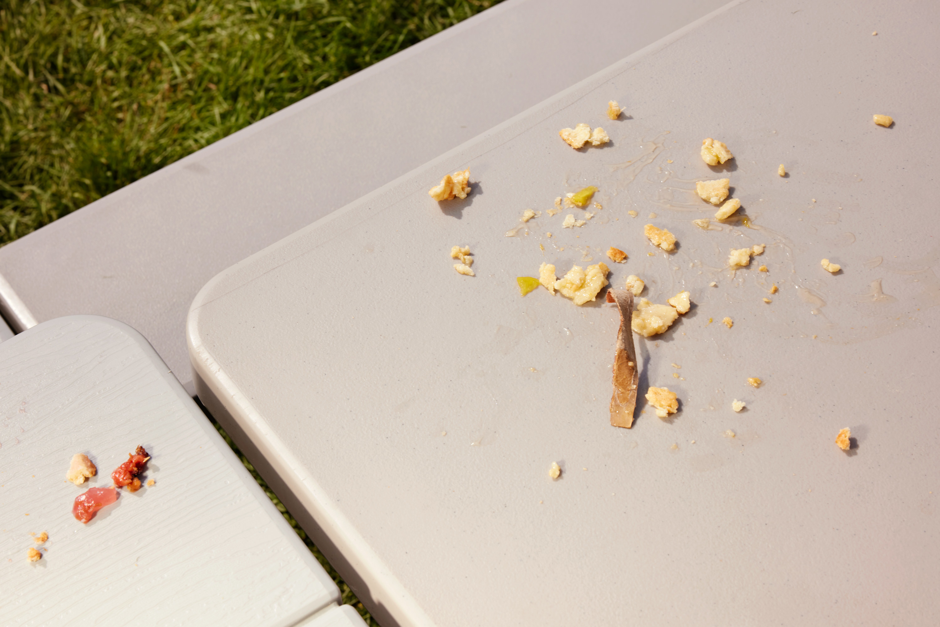 Pie crust and filling smeared on an outdoor picnic table after the contest
