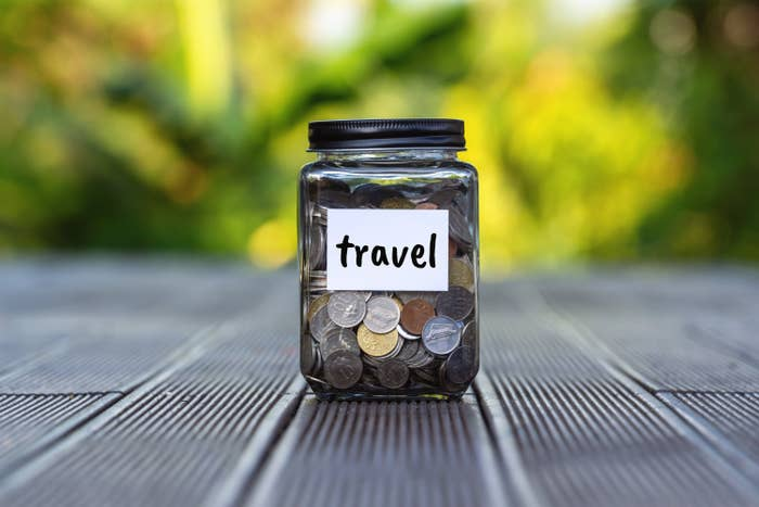 A jar labelled 'travel' filled with coins.